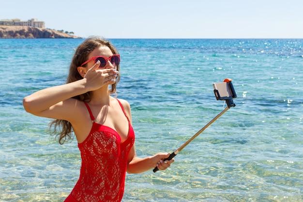 Dziewczyna na plaży z telefonem komórkowym robi selfie na słonecznym dniu Premium Zdjęcia