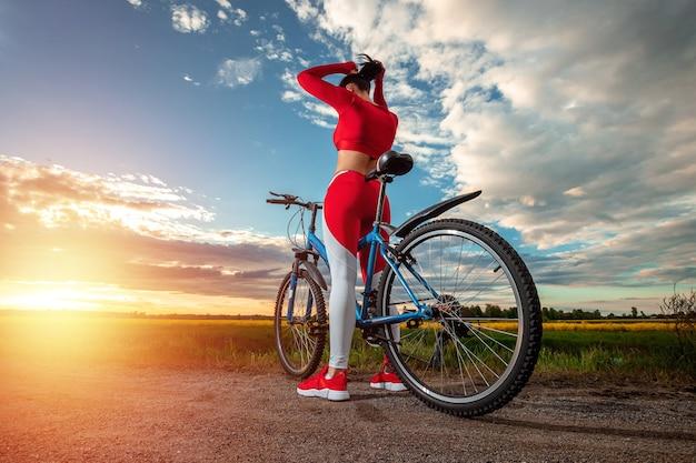 Dziewczyna Na Rowerze Na Tle Zachodu Słońca Premium Zdjęcia