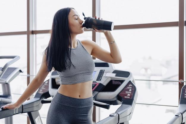 Dziewczyna na siłowni jest szkolona na bieżni i pije wodę Premium Zdjęcia
