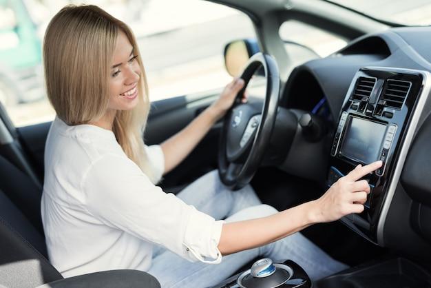 Dziewczyna Naciska Przyciski Na Urządzeniach Sterujących Pojazdu Elektrycznego Premium Zdjęcia