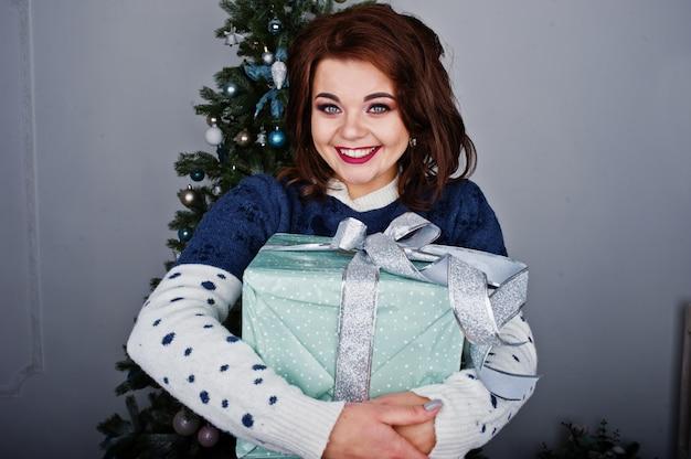 Dziewczyna nosić ciepły sweter z choinką w studio z ozdób choinkowych w rękach. koncepcja szczęśliwych ferii zimowych. Premium Zdjęcia