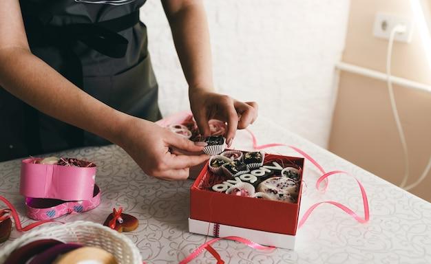 Dziewczyna Pakuje Ciasta W Kolorowe Pudełka Prezentowe. Premium Zdjęcia