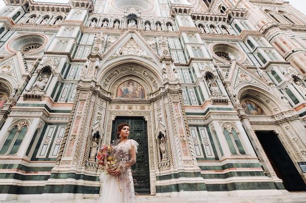 Dziewczyna-panna Młoda Jest Z Pięknym Kwiatowym Wzorem Jako Maską We Florencji, Stylowa Panna Młoda W Sukni ślubnej Stoi Z Maską Na Starym Mieście We Florencji. Modelka We Florencji. Premium Zdjęcia