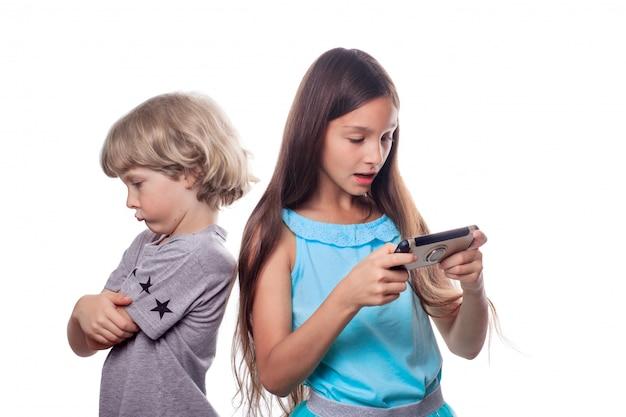 Dziewczyna patrząc na telefon komórkowy i blond chłopiec stojący z wyrazistą obrażoną twarzą Premium Zdjęcia