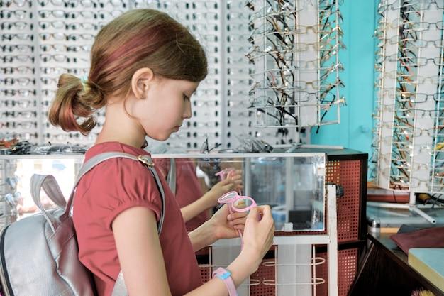 Dziewczyna Patrzeje Szkła I Wybiera, Dziecko Blisko Sklepowego Okno W Eyewear Sklepie Premium Zdjęcia