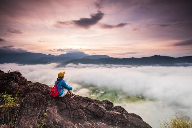 Dziewczyna patrzy na morze mgły na wysokiej górze. Premium Zdjęcia