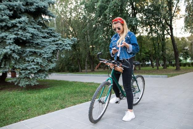Dziewczyna Patrzy Na Trasę Rowerową Na Smartfonie Premium Zdjęcia
