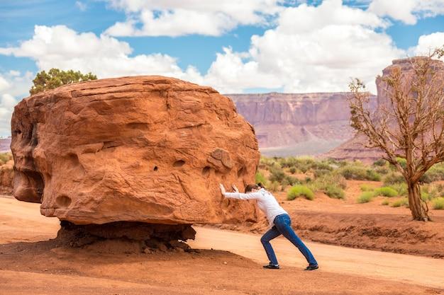 Dziewczyna pchająca duży kamień mocno, niemożliwie i bezużyteczna Premium Zdjęcia