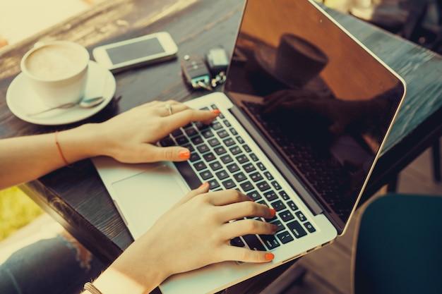 Dziewczyna pisania na laptopie z filiżanką kawy obok niego Premium Zdjęcia