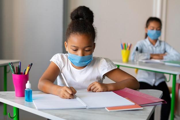 Dziewczyna Pisze W Klasie Mając Na Sobie Maskę Medyczną Darmowe Zdjęcia