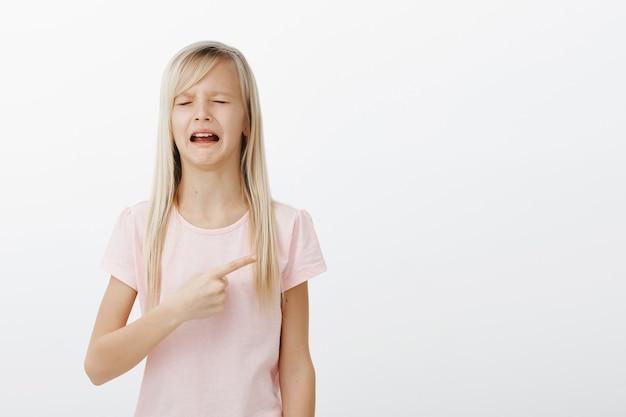 Dziewczyna Płacze I Narzeka, Wskazując W Prawo Darmowe Zdjęcia