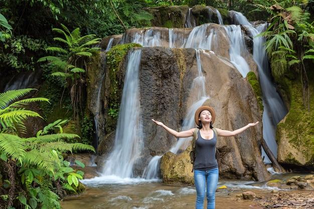 Dziewczyna Podróżuje W Wodospadzie. Dzień Turystyki. Premium Zdjęcia