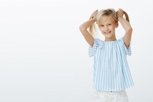 Dziewczyna Pokazuje Znajomym Swoje Nowe Kolczyki. Radosna Zadowolona Mała Dziewczynka O Blond Włosach, Unosząca Włosy Do Góry I Radośnie Uśmiechająca Się Darmowe Zdjęcia