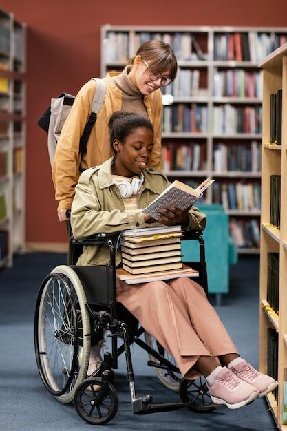 Dziewczyna Pomaga Swojemu Koledze Na Wózku Inwalidzkim Wybrać Książkę Do Projektu Darmowe Zdjęcia