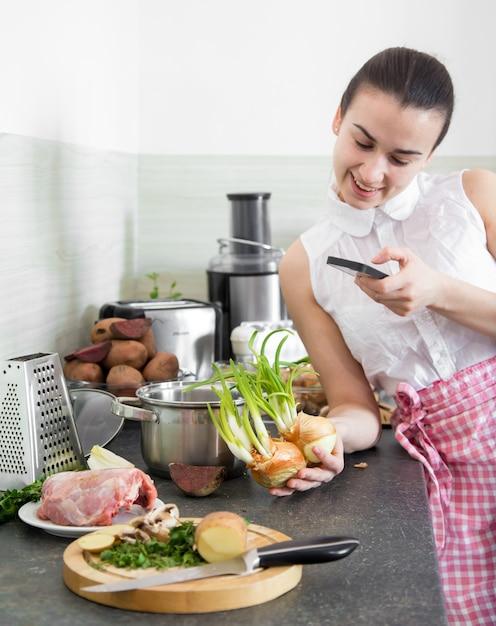 Dziewczyna Przygotowuje Jedzenie W Kuchni Z Telefonem Darmowe Zdjęcia