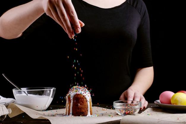 Dziewczyna przygotowuje wielkanocne wypieki, smaruje ciasto polewą i posypuje kolorowym proszkiem Premium Zdjęcia