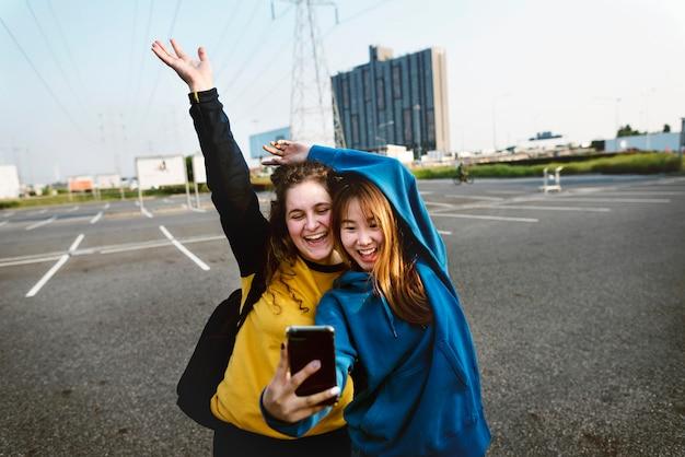 Dziewczyna przyjaciele uśmiecha się i biorąc selfie razem Premium Zdjęcia