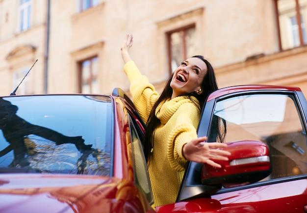 Dziewczyna raduje się w życiu i siedzi w swoim czerwonym samochodzie Darmowe Zdjęcia