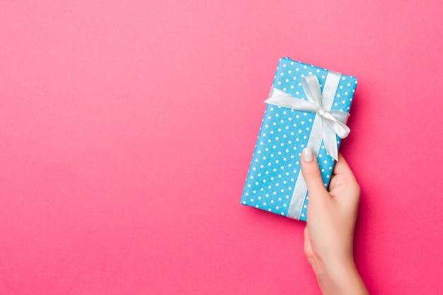 Dziewczyna Ręce Trzyma Papierowe Pudełko Z Prezentem Na Boże Narodzenie Lub Inne święto Na Różowo Premium Zdjęcia