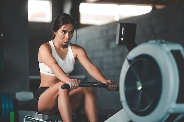 Dziewczyna Robi ćwiczenia Na Maszynie Do Wiosłowania Premium Zdjęcia