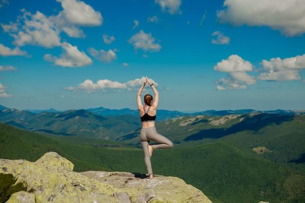 Dziewczyna Robi Joga ćwiczenia Pozycji Lotosu Na Szczycie Góry. Premium Zdjęcia