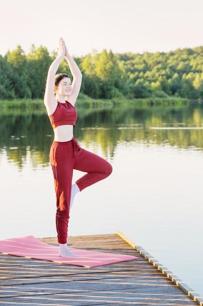 Dziewczyna Robi Joga Na Drewnianym Molo Nad Jeziorem W Lecie Premium Zdjęcia