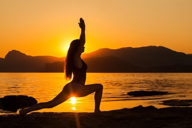 Dziewczyna robi joga nad oceanem. Premium Zdjęcia