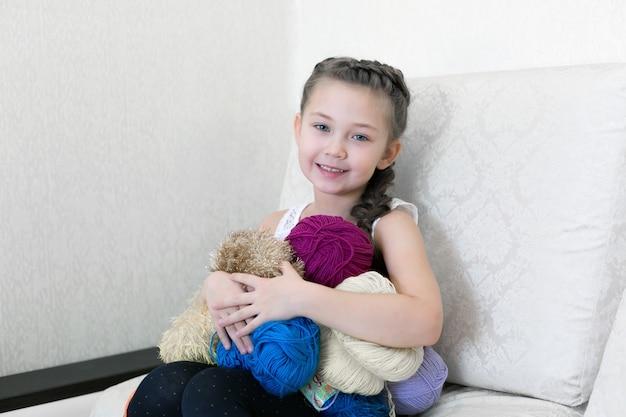 Dziewczyna robi na drutach i na drutach. Premium Zdjęcia