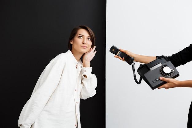 Dziewczyna Rozciąga Się Stary Telefon Podsłucha Nad Czarny I Biały ścianą Darmowe Zdjęcia