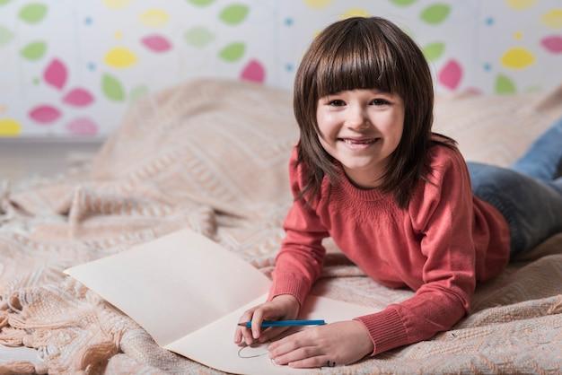Dziewczyna rysunek na papierze na łóżku Darmowe Zdjęcia