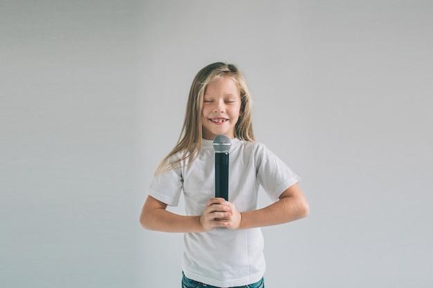 Dziewczyna Się Kołysze. Obraz Dziecka śpiewającego Do Mikrofonu Premium Zdjęcia