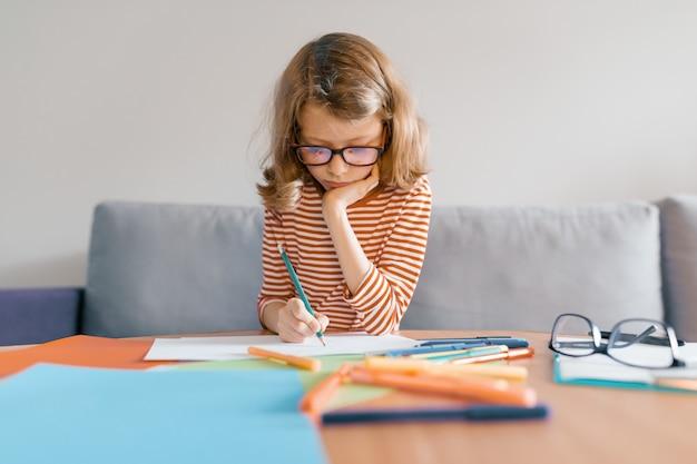 Dziewczyna siedzi na kanapie w domu rysuje pisze ołówkiem na papierze. Premium Zdjęcia