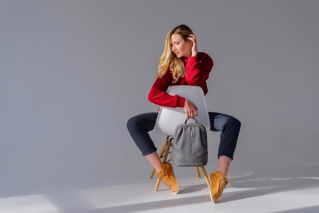 Dziewczyna Siedzi Na Krześle I Trzyma Szary Plecak Premium Zdjęcia