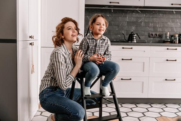 Dziewczyna Siedzi Na Schodach, A Jej Matka Pozuje Obok Na Tle Kuchni. Darmowe Zdjęcia