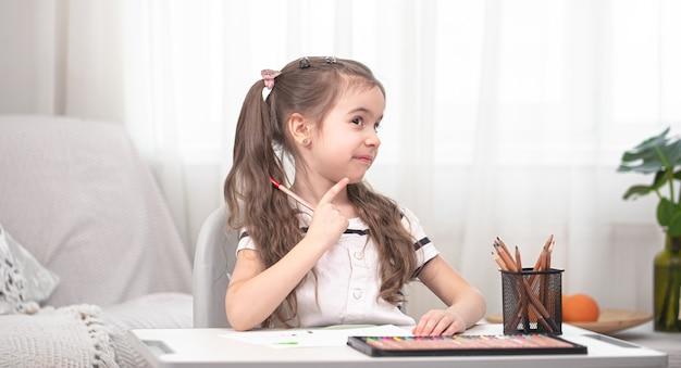 Dziewczyna Siedzi Przy Stole I Odrabia Lekcje. Dziecko Uczy Się W Domu. Nauka W Domu. Miejsce Na Tekst. Darmowe Zdjęcia
