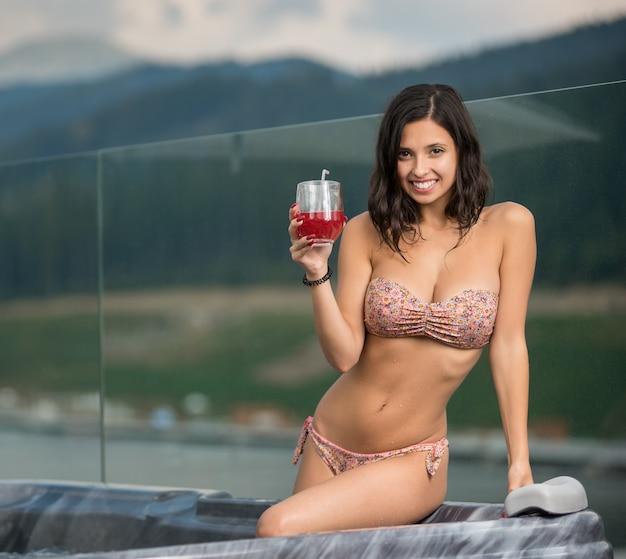 Dziewczyna siedzi w jacuzzi przy koktajlu Premium Zdjęcia