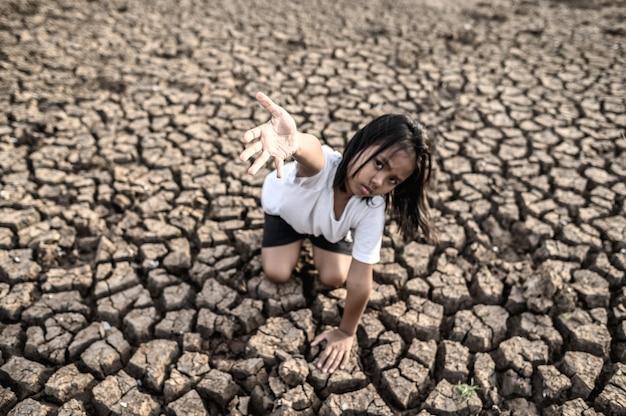Dziewczyna siedziała gdzie indziej, ręką w niebo, żeby prosić o deszcz na suchej ziemi, globalne ocieplenie Darmowe Zdjęcia