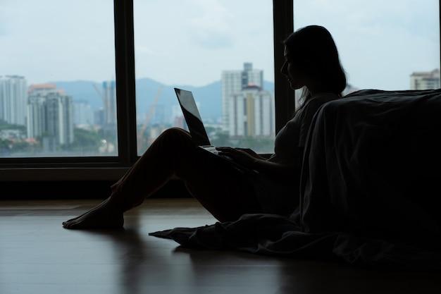Dziewczyna Siluet Pracująca Na Laptopie I Pijąca Kawę, Siedząca Na Podłodze Przy łóżku Przy Panoramicznym Oknie Z Pięknym Widokiem Z Wysokiej Podłogi. Stylowe Nowoczesne Wnętrze. Przytulne Miejsce Pracy Premium Zdjęcia