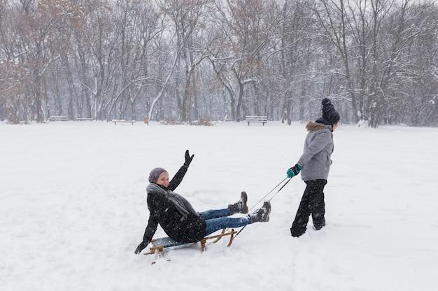 Dziewczyna sledding jej matki przy zima parkiem Darmowe Zdjęcia