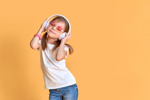 Dziewczyna Słucha Muzyka W Hełmofonach Na Kolorze żółtym. Słodkie Dziecko Korzystających Z Szczęśliwej Muzyki Tanecznej, Zamknij Oko I Uśmiech Pozowanie Premium Zdjęcia