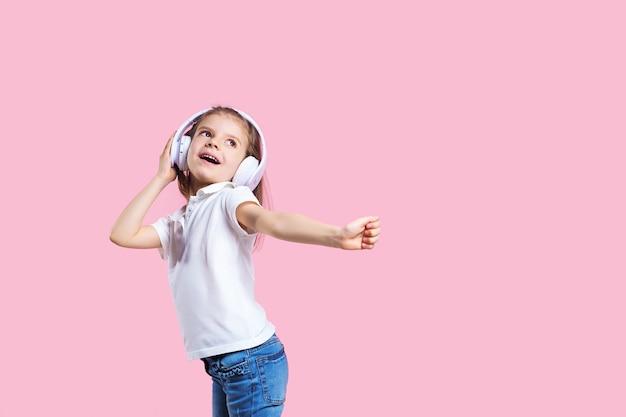 Dziewczyna Słucha Muzyka W Hełmofonach Na Menchiach. Słodkie Dziecko Korzystających Z Szczęśliwej Muzyki Tanecznej, Zamknij Oko I Uśmiech Pozowanie Premium Zdjęcia