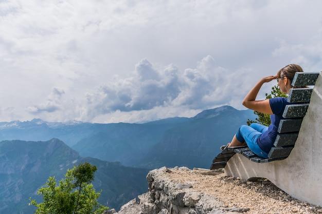 Dziewczyna spoczywa na szczycie góry, siedząc na niezwykłej ławce. Premium Zdjęcia