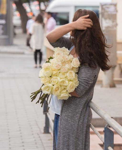 Dziewczyna Stoi Na Ulicy Z Bukietem Białych Róż Darmowe Zdjęcia