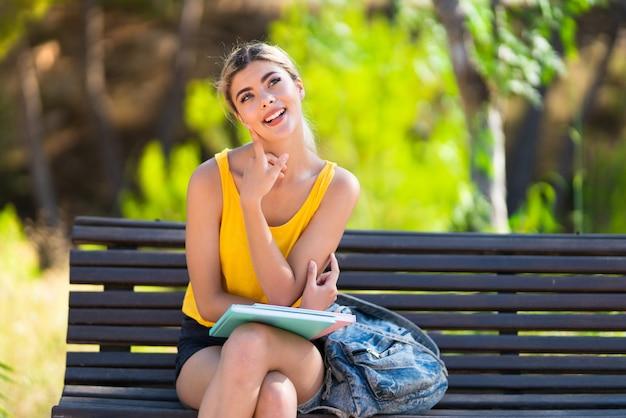 Dziewczyna student na zewnątrz myśli pomysł, patrząc w górę Premium Zdjęcia