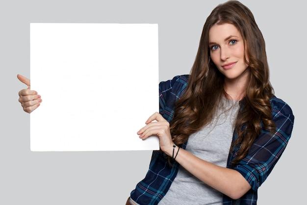 Dziewczyna trzyma białego billboard Darmowe Zdjęcia