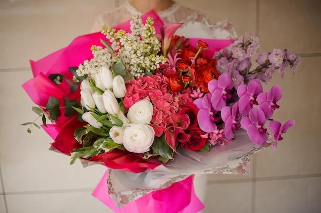 Dziewczyna Trzyma Bukiet Białych Tulipanów I Bzu, Różowe Orchidee I Hortensje Oraz Czerwone Róże Premium Zdjęcia
