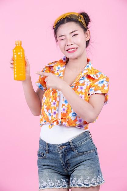 Dziewczyna trzyma butelkę soku pomarańczowego na różowym tle. Darmowe Zdjęcia