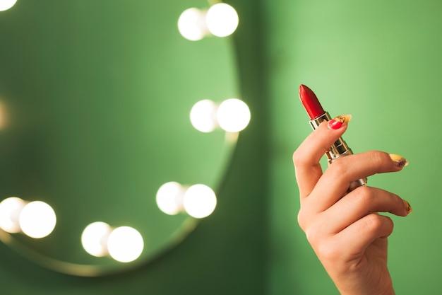 Dziewczyna trzyma czerwoną szminkę przed lustrem Darmowe Zdjęcia