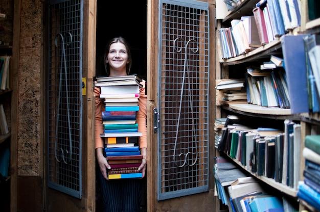Dziewczyna Trzyma Duży Stos Książek I Ma W Bibliotece Dużo Literatury Premium Zdjęcia