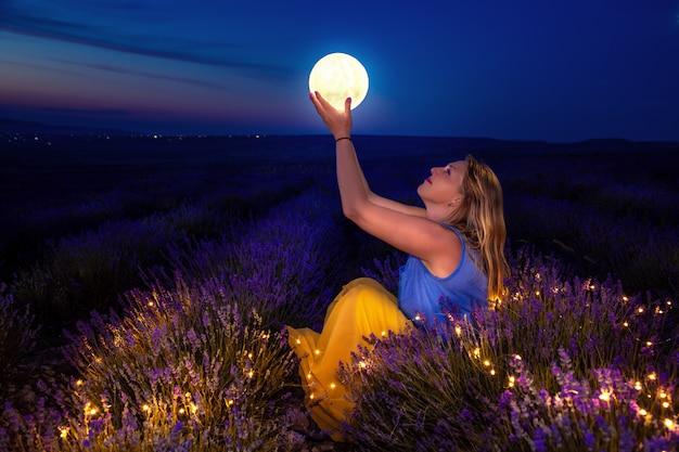 Dziewczyna trzyma księżyc w dłoniach. lawendowe pole w nocy. Premium Zdjęcia
